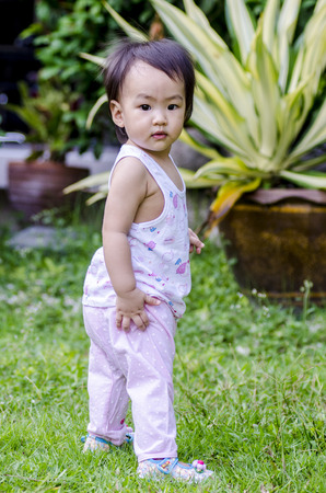Lovely baby girl standing and trying to walk