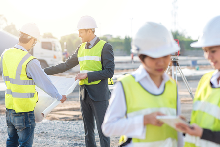 Engineer and builder review blueprint during team meeting at construction site in the morning with sunlight