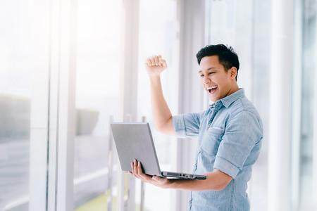 Foto de Happy excited Asian man holding laptop and raising his arm up to celebrate success or achievement. - Imagen libre de derechos