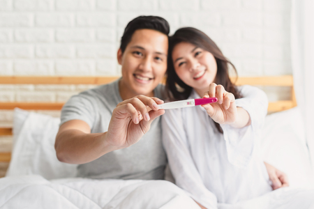 Foto de Shot of happy Asian couple showing a positive pregnancy test in bedroom. Focus on pregnancy test device. - Imagen libre de derechos