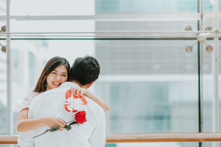 Foto de Happy  beautiful young Asian woman embracing her boyfriend after receive valentine gift and rose - Imagen libre de derechos