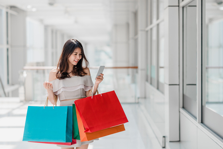 Foto de Beautiful young happy Asian woman with colorful shopping bag using smartphone while shopping in mall - Imagen libre de derechos