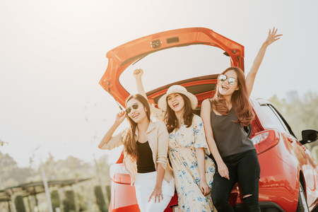 Photo for Three happy Asian girl best friends traveler celebrating a good time with arm up while sitting in car trunk  - Royalty Free Image