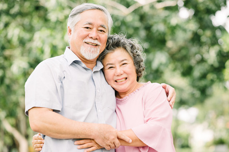 Foto de Happy Asian senior couple smiling while holding each other outdoor in the park. - Imagen libre de derechos