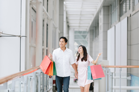 Foto de Happy Asian couple holding colorful shopping bags and enjoying shopping, having fun together in mall. Consumerism, love, dating, lifestyle concept - Imagen libre de derechos