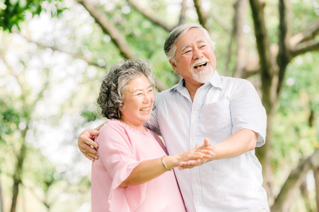 Photo for Happy senior Asian couple dancing in the park in sunny day - Royalty Free Image