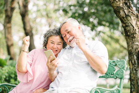 Foto de Happy senior Asian couple laughing and celebrating success together with smartphon in park - Imagen libre de derechos