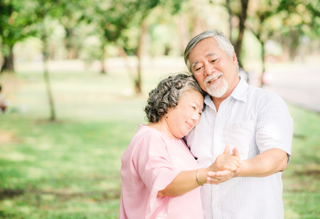 Foto de Happy senior Asian couple in love dancing in the park in sunny day - Imagen libre de derechos