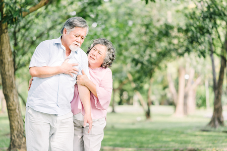 Photo pour Senior Asian man holding his chest and feeling pain suffering from heart attack outdoor at the park while his wife feeling concern - image libre de droit