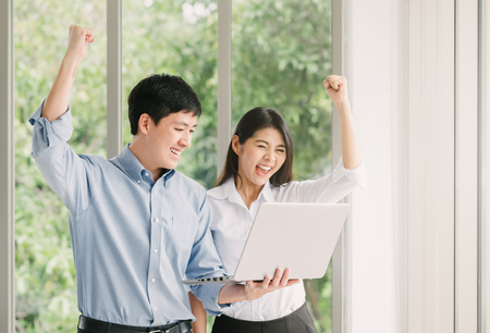 Photo pour Young Asian couple celebrating success with arms up while wacthing laptop indoor - image libre de droit