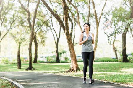 Foto de Beautiful young healthy Asian woman running in the park - Imagen libre de derechos