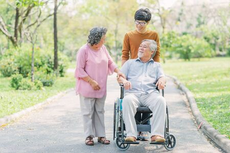 Photo for Happy senior Asian man in wheelchair with his wife and son walking in park. aging society concept. - Royalty Free Image