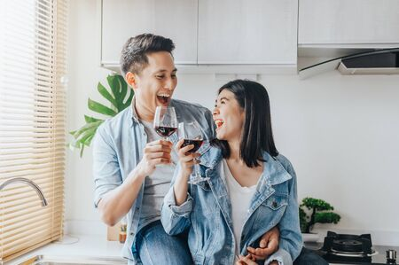 Photo pour Happy Asian couple in love laughing and drinking red wine in the kitchen to celebrate their anniversary - image libre de droit