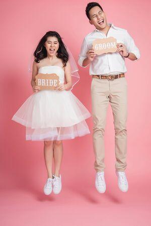 Foto de Happy Asian bride and groom in casual wedding dress jumping make funny face with eye close over pink background  - Imagen libre de derechos
