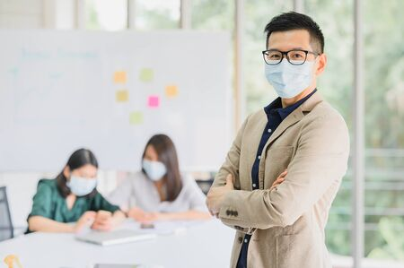 Photo pour Happy Asian man entrepreneur wears face mask standing arms crossed with confident, with a colleague in background in meeting room at modern office  - image libre de droit