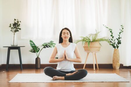 Photo pour Shot of attractive healthy Asian woman doing yoga meditation at home in living room - image libre de droit