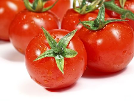 closeup image of red tomatoes on white plane