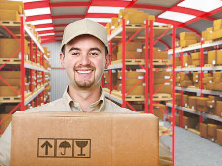 smiling young delivery man in modern warehouse