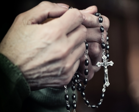 closeup on female hands with classic rosary