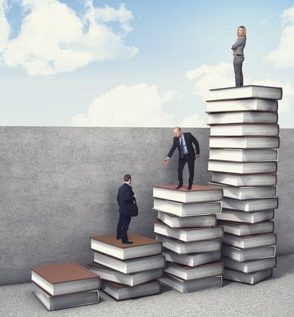 Foto de business people on 3d books piles - Imagen libre de derechos