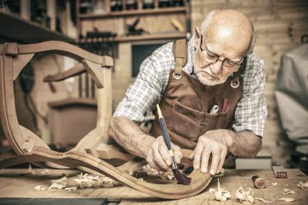 Photo pour elderly carpenter uses a brush on an unfinished chair - image libre de droit