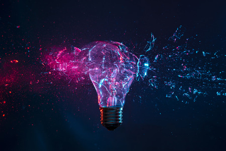 Photo for detail of the explosion of a filament light bulb, high speed photography. Studio shot with purple and blue artificial light on a dark background. - Royalty Free Image