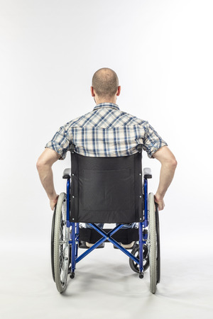 Photo pour Man sitting on a wheelchair because he is injured. white background and back view. Concept of disability and medical support. - image libre de droit