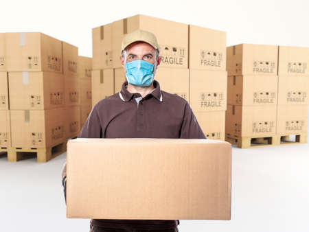 Photo for courier with mask and parcel in hand, pallet of cartons in the background. - Royalty Free Image