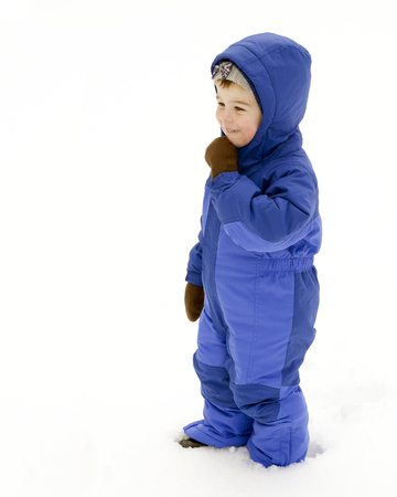 A young boy plays outside in the snow wearing a blue snowsuit
