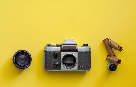 Photo for Flat lay view of retro camera, lens and film strip over pastel coloured yellow background with copy space, pop art minimal style - Royalty Free Image