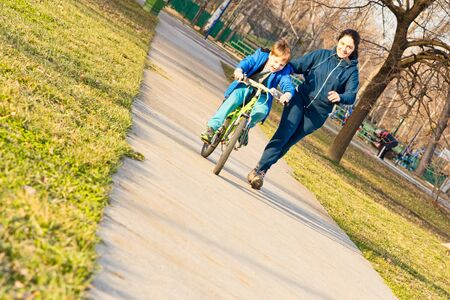 Foto de Little toddler boy learning to ride a bike with his mother. - Imagen libre de derechos