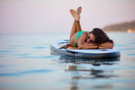 Photo pour Young, attractive brunette woman, wearing turquoise bikini, posing on a stand up paddle board, Aegean sea, Thasos, Greece. - image libre de droit