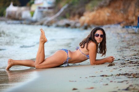 Photo pour Attractive young brunette woman lying down on the beach on the island of Thasos, Greece. - image libre de droit