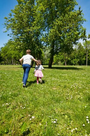 Photo for Brother and sister, 9 and 4 years old, running outdoors on green grass in spring time. - Royalty Free Image