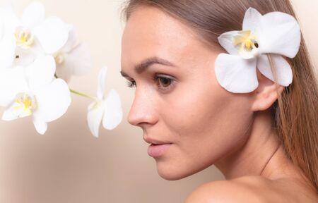Foto de Closeup portrait of a beautiful model with white orchid flowers. - Imagen libre de derechos