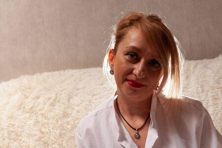 Photo pour Portrait of an attractive middle-aged woman. Homemade portrait on the couch, middle-aged blonde. - image libre de droit