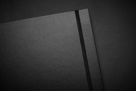 Photo pour Blank black notebook on a black table, mockup photo. Blank black cover template with copy space for design. Black on black, minimal design concept. - image libre de droit