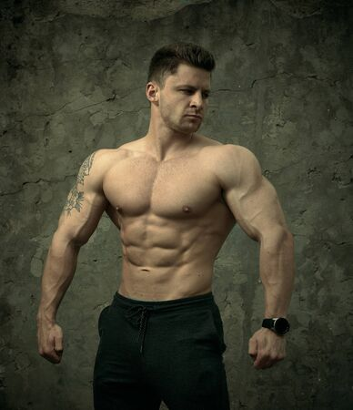 Photo for Handsome muscular man posing on concrete wall background. The concept of fitness, bodybuilding, health, lifestyle. Portrait of fitness fitness model. - Royalty Free Image
