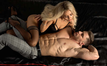 Photo pour Young attractive sexy couple has sex in bed. Beautiful blonde in black lingerie with a muscular guy. - image libre de droit
