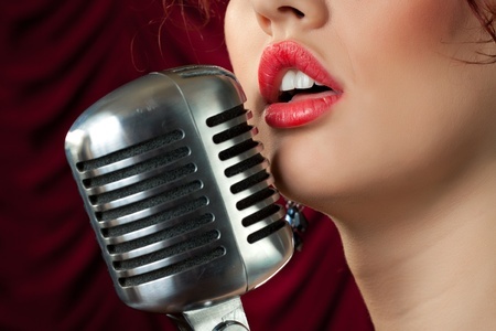 woman with red lips singing in vintage microphone