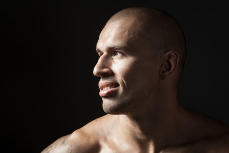 portrait of strong smiling man isolated on black background with copyspace