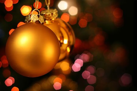 Christmas golden ball with a light blur creating bokeh in the background, natural zoom effect