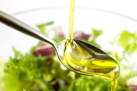 Foto de Pouring olive oil in the salad over a spoon - Imagen libre de derechos