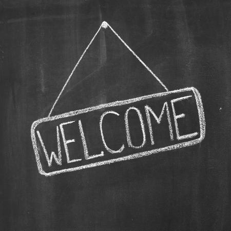 Word Welcome written by a chalk on a blackboard