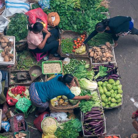 Foto de BALI, INDONESIA - NOVEMBER 3, 2016: Balinese women selling the vegetables on the main market of Ubud, top view - Imagen libre de derechos