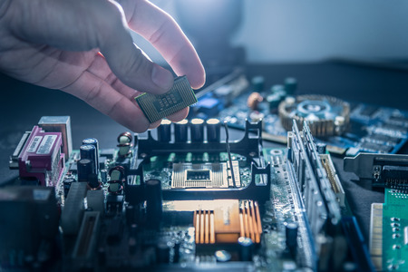 Photo for The technician is putting the CPU on the socket of the computer motherboard. - Royalty Free Image