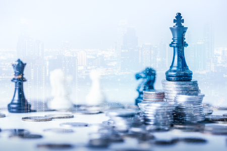 Foto de double exposure image of the coin stack which has the Staunton chess set such as king on top and overlay with cityscape image. the concept of accounting, business, financial, economy and investment. - Imagen libre de derechos