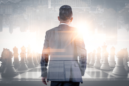 Foto de The double exposure image of the businessman thinking overlay with chess game and cityscape image and white copy space. the concept of strategic, planning, management, intelligence and education. - Imagen libre de derechos