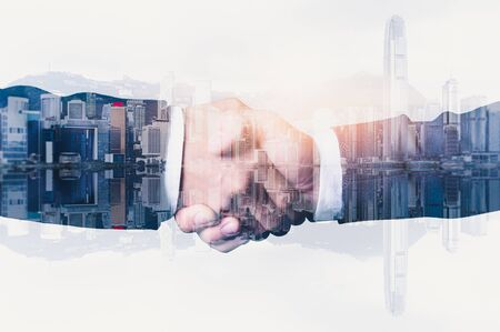 Foto de The double exposure image of the businessman handshaking with another one during sunrise overlay with cityscape image. The concept of modern life, business, city life and partnership. - Imagen libre de derechos