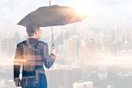 Photo pour The double exposure image of the Businessmen are spreading umbrella during sunrise overlay with cityscape image. The concept of modern life, business, insurance and protection. - image libre de droit